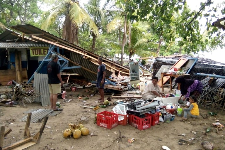 """People gather salvageable items from damaged buildings on Carita beach on December 23, 2018, after the area was hit by a tsunami that may have been caused by the Anak Krakatoa volcano. - At least 43 people have been killed and nearly 600 injured in a tsunami in Indonesia that may have been caused by a volcano known as the """"child"""" of the legendary Krakatoa, officials said on December 23. (Photo by Semi / AFP)SEMI/AFP/Getty Images"""