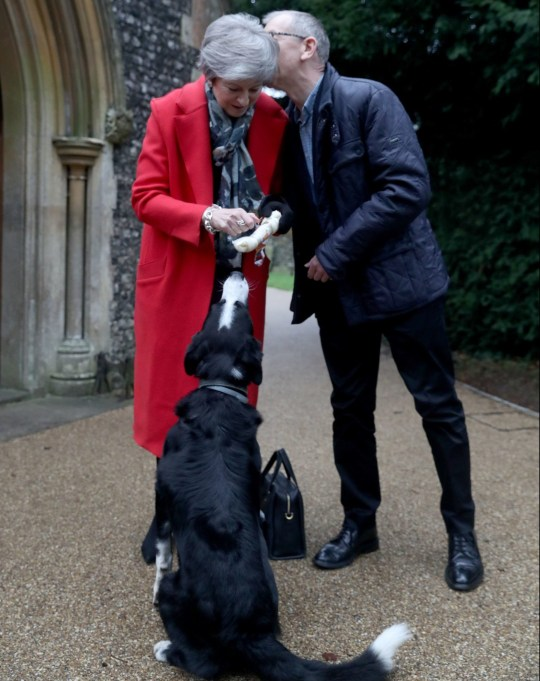 Prime Minister Theresa May gives a dog called Blitz a Christmas gift as she arrives with her husband Philip May to attend the morning Christmas Day service at a church near her constituency home. PRESS ASSOCIATION Photo. Picture date: Tuesday December 25, 2018. See PA story POLITICS May. Photo credit should read: Steve Parsons/PA Wire