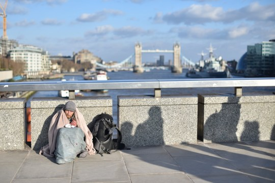 LONDON, ENGLAND - MARCH 19: A homeless person wrapped in a blanket sits holding a cup on London Bridge as shadows of people walk past as the rush hour begins on March 19, 2018 in London, England. (Photo by John Keeble/Getty Images)