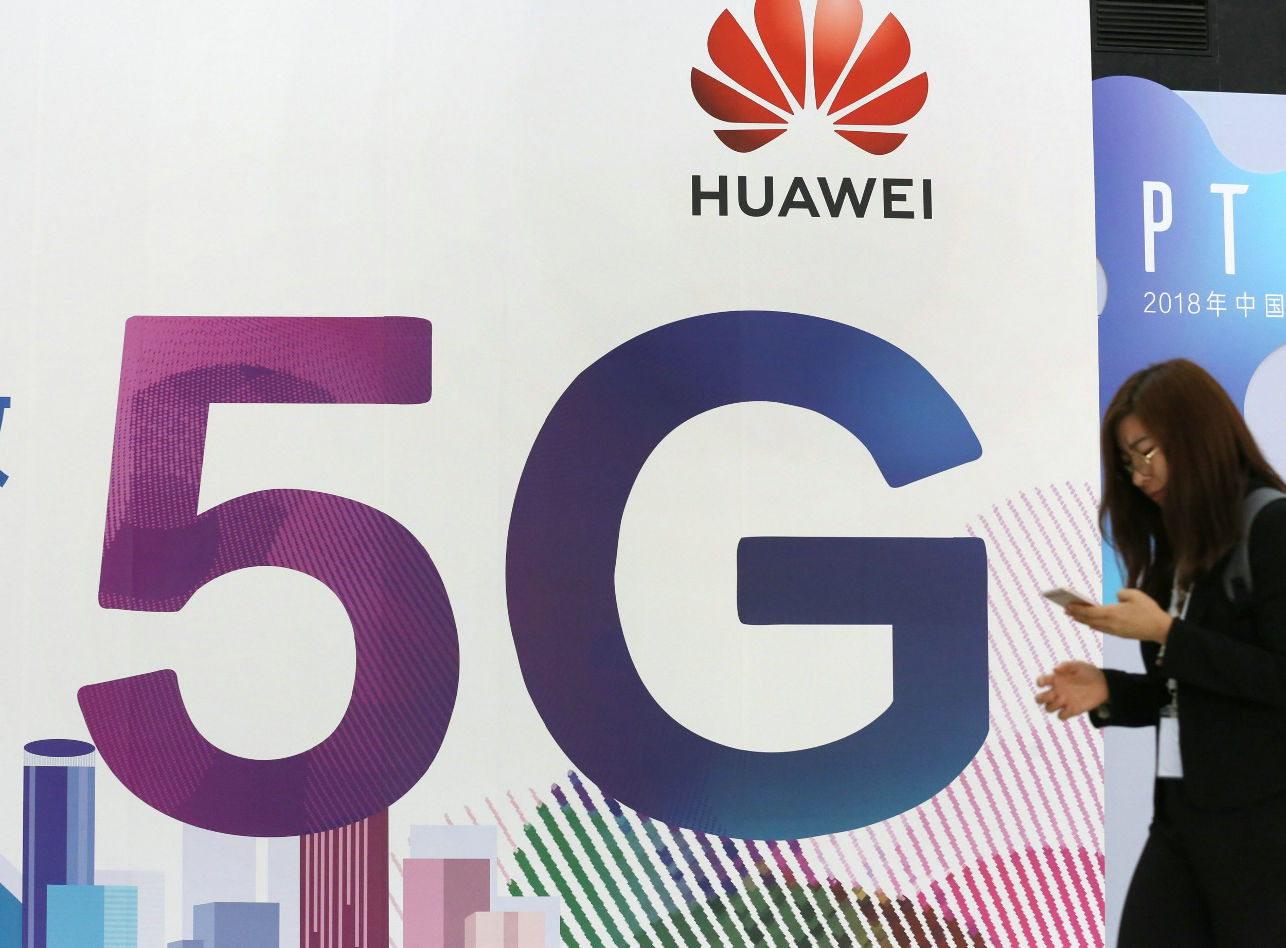 BEIJING, CHINA - SEPTEMBER 26: A woman walks past the stand of Huawei featuring 5G technology during the PT Expo China at Beijing National Convention Center on September 26, 2018 in Beijing, China. (Photo by VCG/VCG via Getty Images)