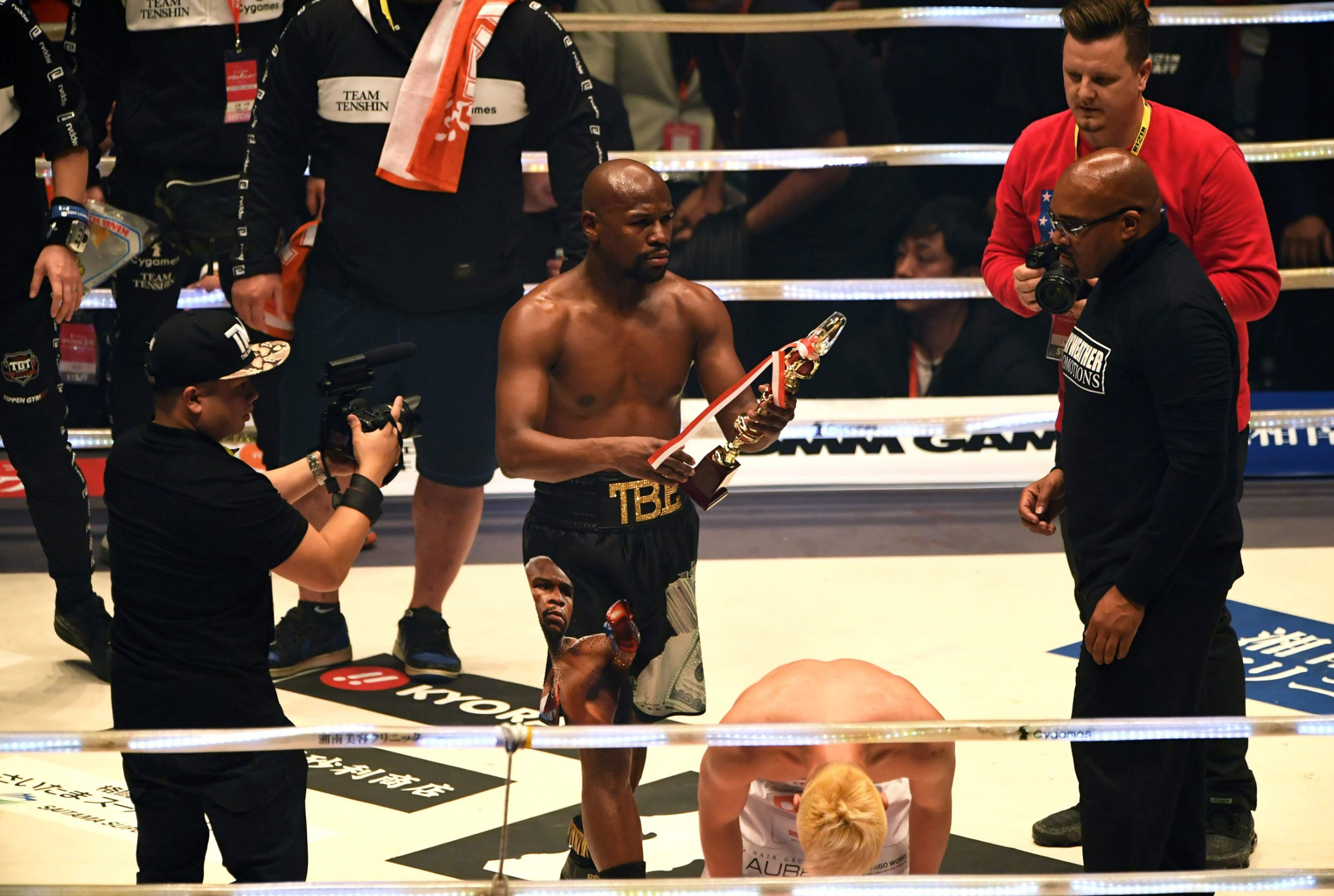 """US boxing legend Floyd Mayweather Jr (c) holds the trophy after winning the exhibition fight against Tenshin Nasukawa of Japan (C-R)) at Saitama Super Arena in Saitama on December 31, 2018. - Floyd Mayweather beat Japanese kickboxing phenomenon Tenshin Nasukawa by a technical knock-out in the first round of a New Year's Eve """"exhibition"""" bout that brought the US boxing superstar out of retirement. (Photo by Toshifumi KITAMURA / AFP)TOSHIFUMI KITAMURA/AFP/Getty Images"""