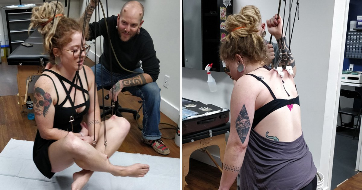 Piercing addict suspended from metal hooks in her back
