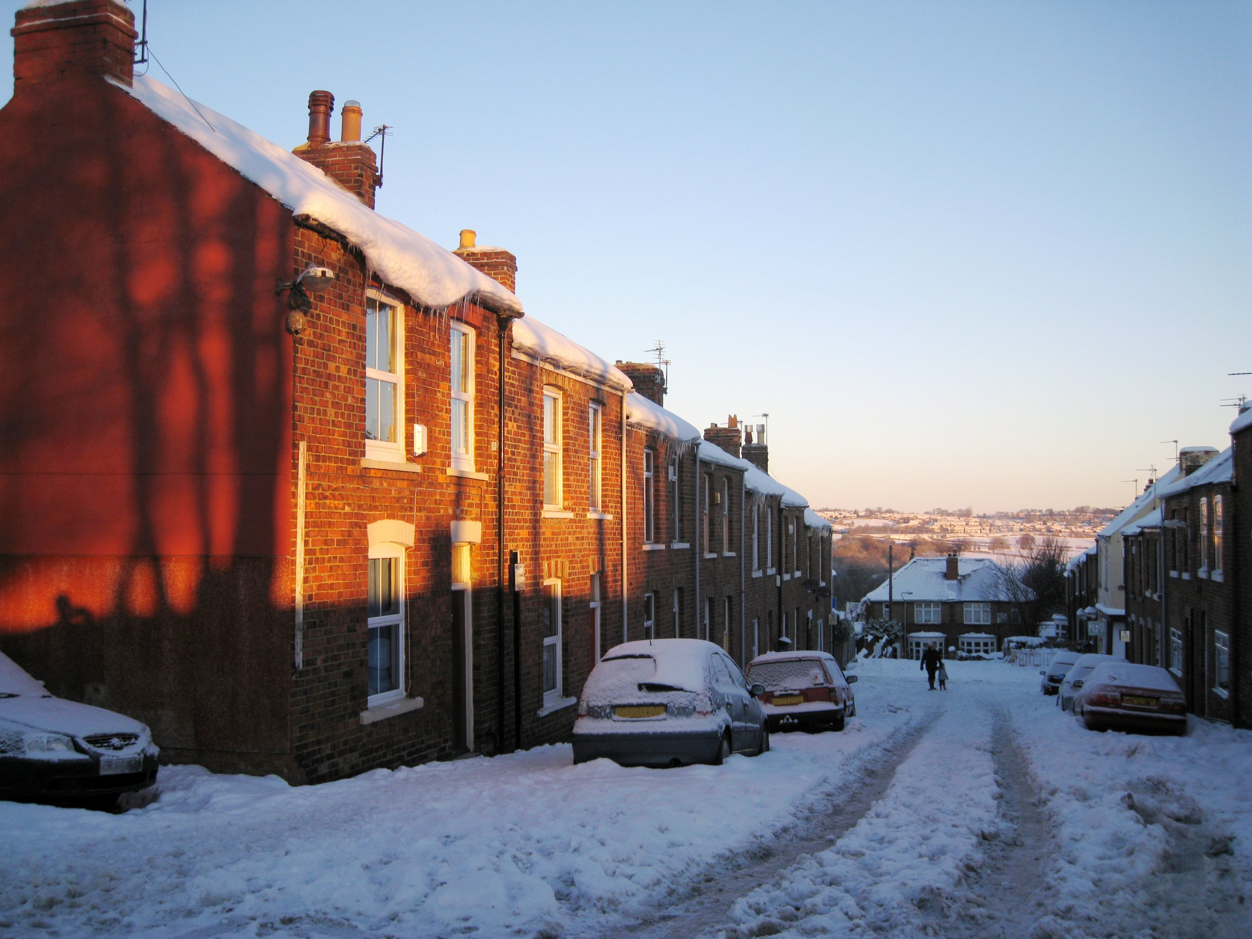 Sun rises over a street of victorian red brick terraced houses with thick snow covering everything and icicles hanging off the houses; Shutterstock ID 674655259; Purchase Order: -
