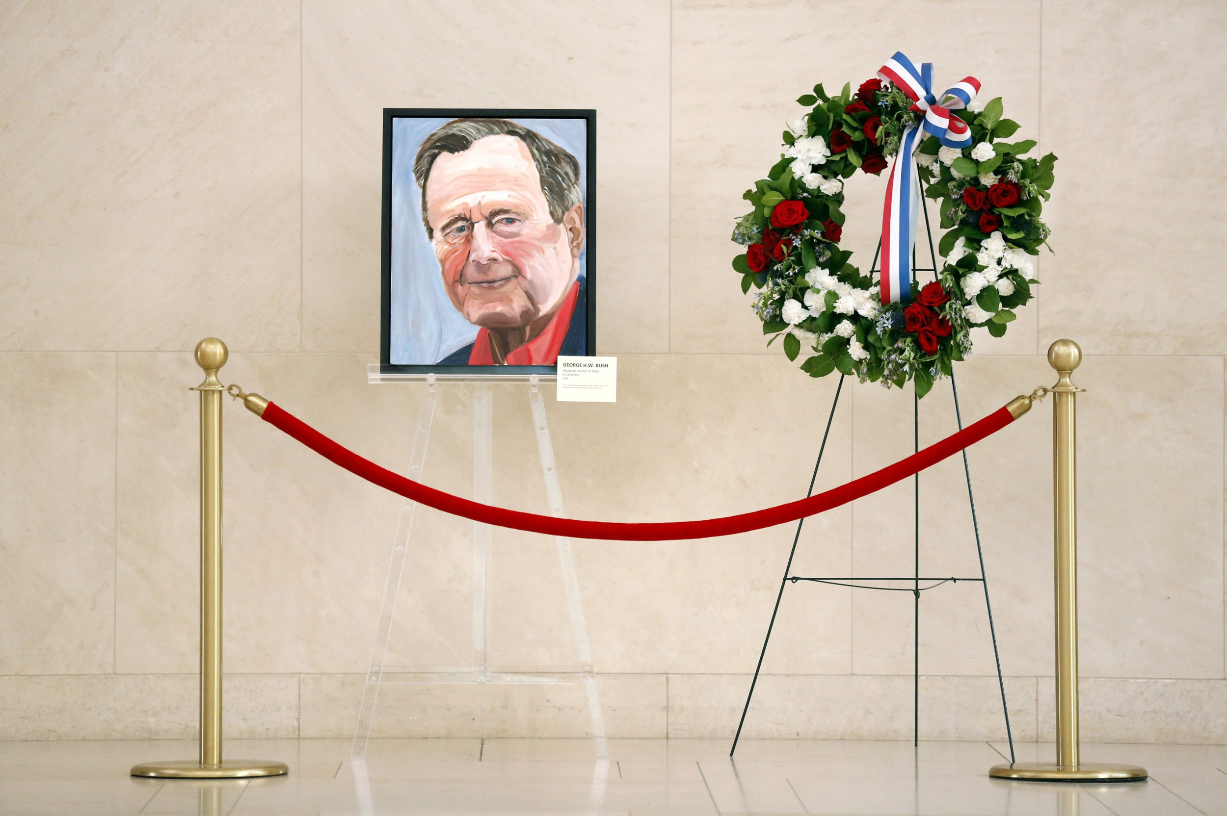 A painted portrait of the late 41st President George H.W. Bush -- painted by his son, Pres. George W. Bush -- and a memorial wreath grace the atrium area of his son's George W. Bush Presidential Library and Museum in University Park, Texas, Sunday, Dec. 2, 2018. President George H.W. Bush died last week in Maine. The painting was done by his son and former 43rd President George W. Bush. Bush will be laid to rest next to his wife Barbara at the George H.W. Bush Library Center in College Station, Texas this week. (Tom Fox/The Dallas Morning News via AP)