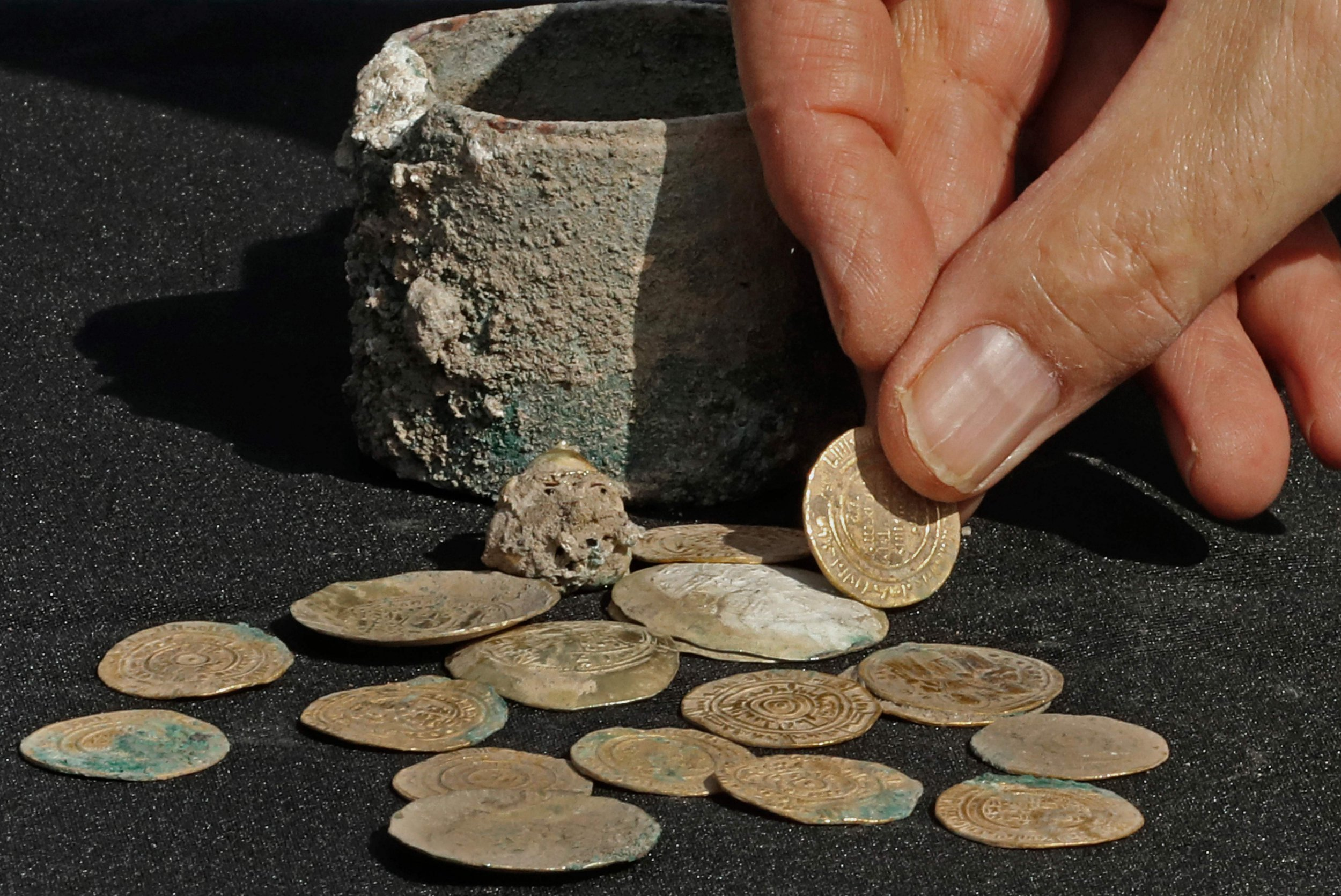 A picture taken on December 3, 2018, shows ancient gold coins and an earring recently uncovered at an excavation site in the Israeli Mediterranean town of Caesarea. - A treasure of 24 rare gold coins consisting of 18 Fatimid dinars, which were the standard local currency during that time (909-1171), as well as six are Byzantine coins, which include five dating to the era of Byzantine Emperor Michael VII Doukas (1071-1078), was recently uncovered in Caesarea. (Photo by JACK GUEZ / AFP)JACK GUEZ/AFP/Getty Images