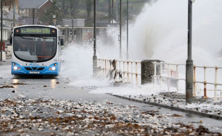 A bus is driven along the coast road, as waves break over the shore in Carnlough, Northern Ireland, on November 28, 2018. - Britain's Met Office issued warnings for high winds as Storm Dianna, named by the Portuguese authorities, started to impact the United Kingdom. (Photo by Paul FAITH / AFP) (Photo credit should read PAUL FAITH/AFP/Getty Images)