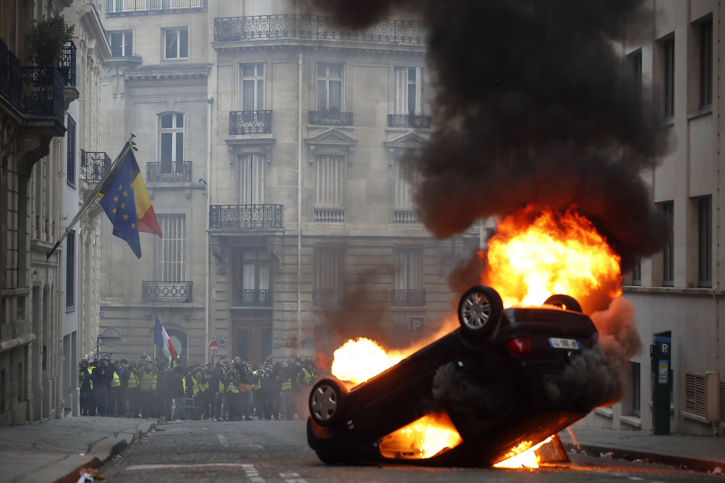 epa07217247 Yellow Vests (Gilets jaunes) protesters are seen behind a burning overturned car near Avenue Marceau during the demonstration in Paris, France, 08 December 2018. The so-called 'gilets jaunes' (yellow vests) is a protest movement, which reportedly has no political affiliation, that continues protests across the nation over high fuel prices. EPA/IAN LANGSDON