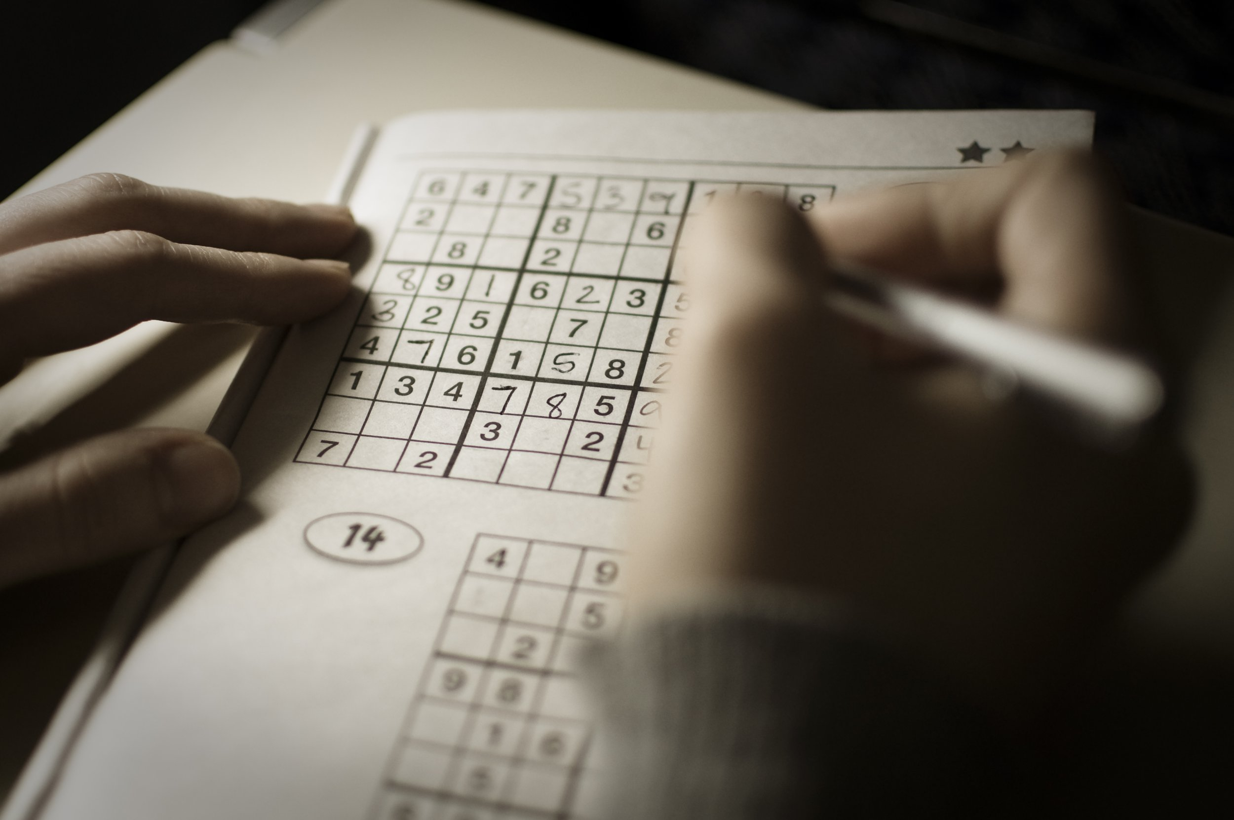 Woman's hands holding pen and playing Sudoku.