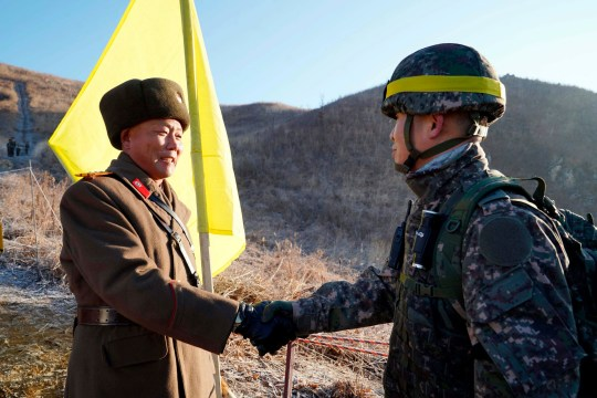 In this photo provided by South Korea Defense Ministry, South Korean army Col. Yun Myung-shick, right, shakes hands with North Korean army Lt. Col. Ri Jong Su before crossing the Military Demarcation Line inside the Demilitarized Zone (DMZ) to inspect the dismantled North Korean guard post in the central section of the inter-Korean border in Cheorwon, Wednesday, Dec. 12, 2018. Dozens of North and South Korean soldiers crossed over the world's most heavily armed border Wednesday as they inspected the sites of their rival's front-line guard posts to verify they'd been removed, part of inter-Korean engagement efforts that come amid stalled U.S.-North Korea nuclear disarmament talks. (South Korea Defense Ministry via AP)