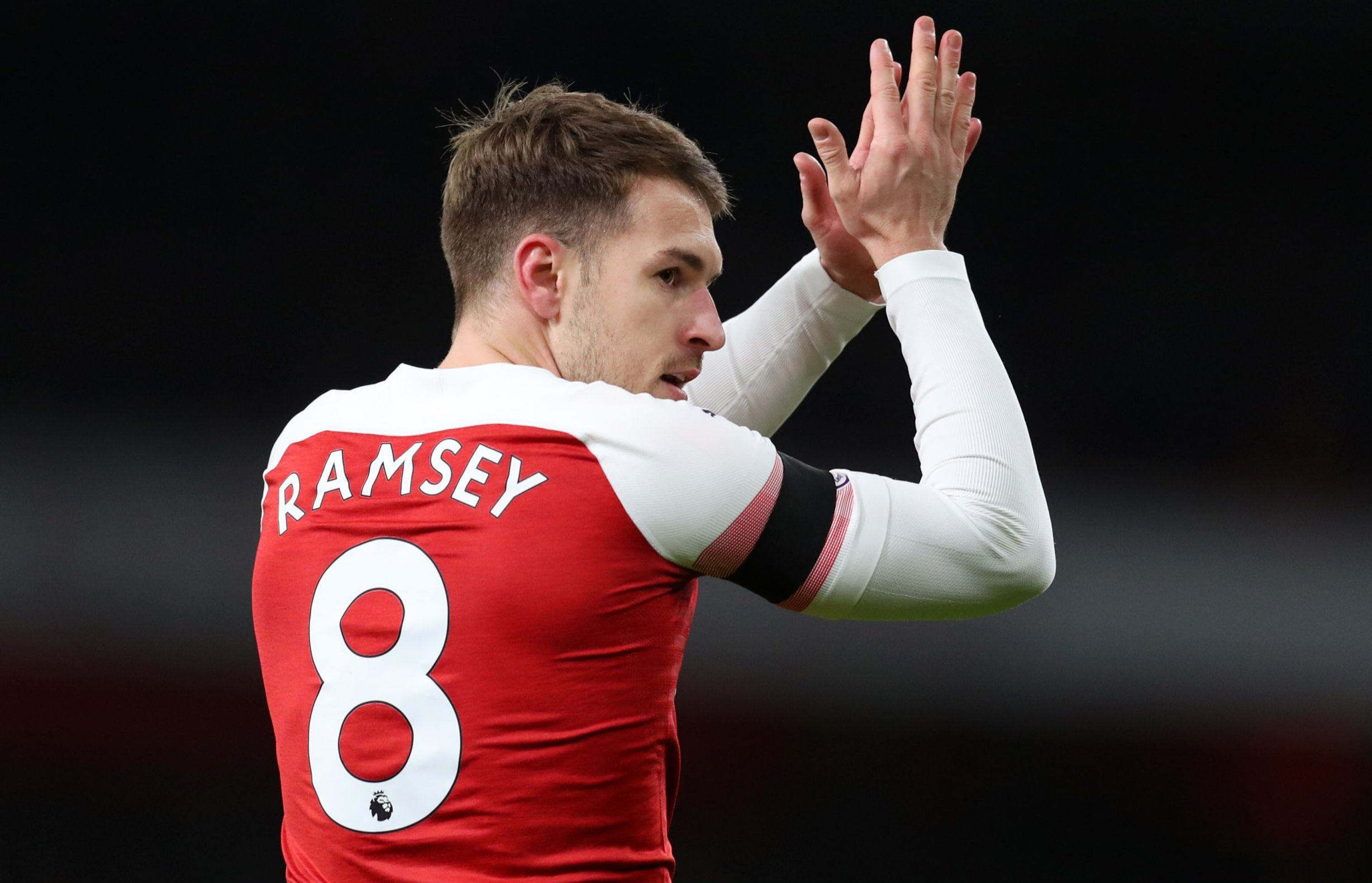Aaron Ramsey wearing Arsenal home kit with number 8 on his shirt celebrates after scoring a goal against Fulham