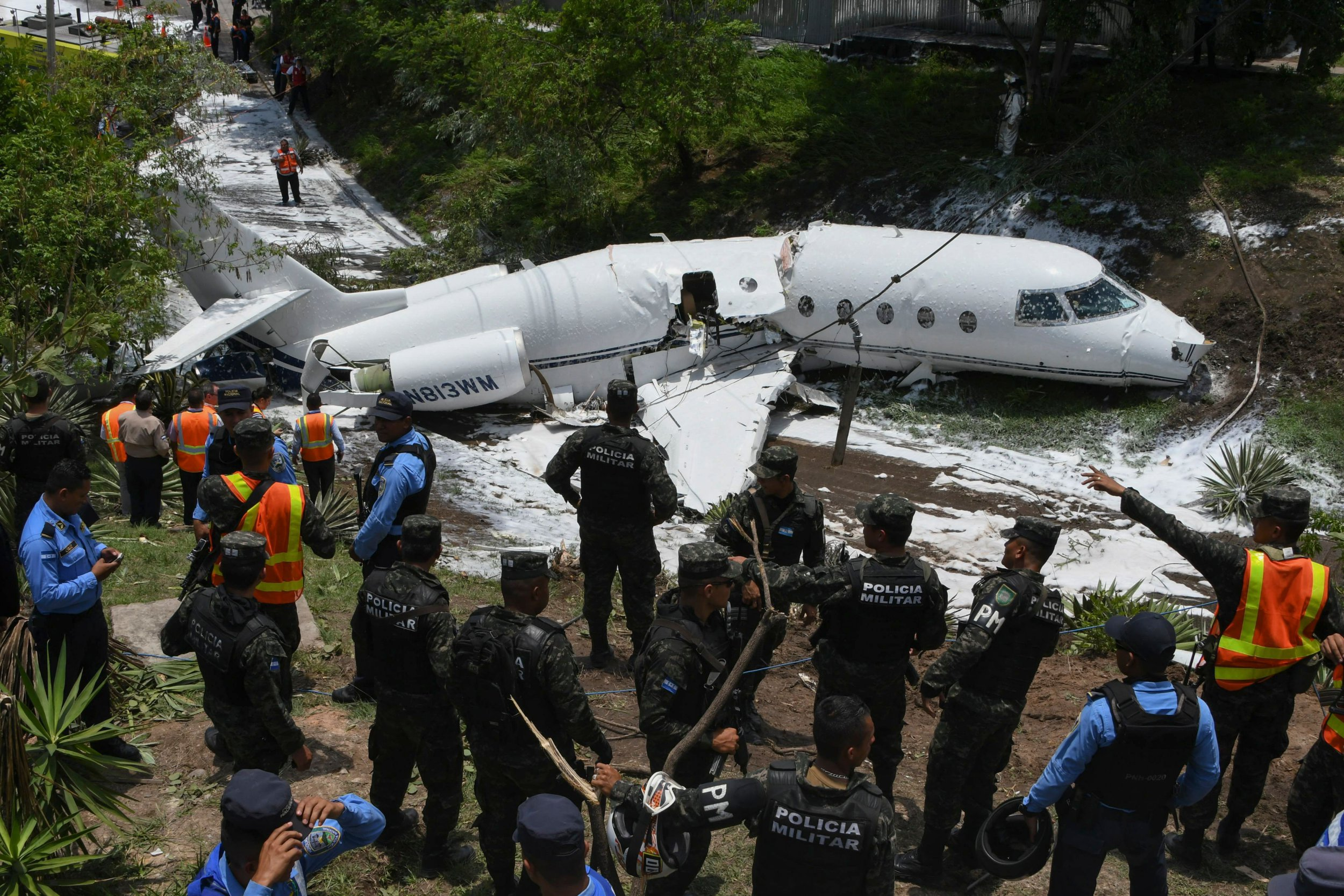 TOPSHOT - Emergency personnel, Honduran soldiers and police officers work at the site of an accident, after a plane went off the runway at Toncontin International airport and collapsed over a busy boulevard in Tegucigalpa on May 22, 2018. - At least six US passengers were injured in the accident. (Photo by Orlando SIERRA / AFP) (Photo credit should read ORLANDO SIERRA/AFP/Getty Images)
