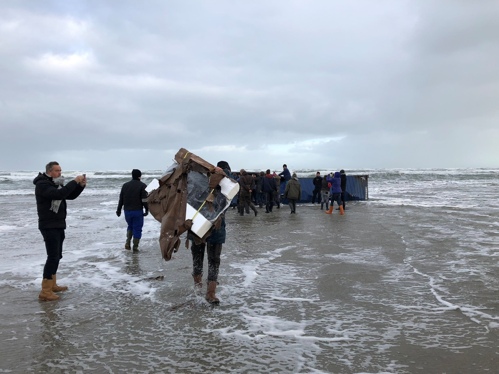 A person carries a flat-screen television set as others inspect a cargo container after it washed up on a beach in Terschelling, Netherlands January 2, 2019 in this image obtained from social media. Erik Scheer via REUTERS ATTENTION EDITORS - THIS IMAGE WAS PROVIDED BY A THIRD PARTY. NO RESALES. NO ARCHIVES. MANDATORY CREDIT.