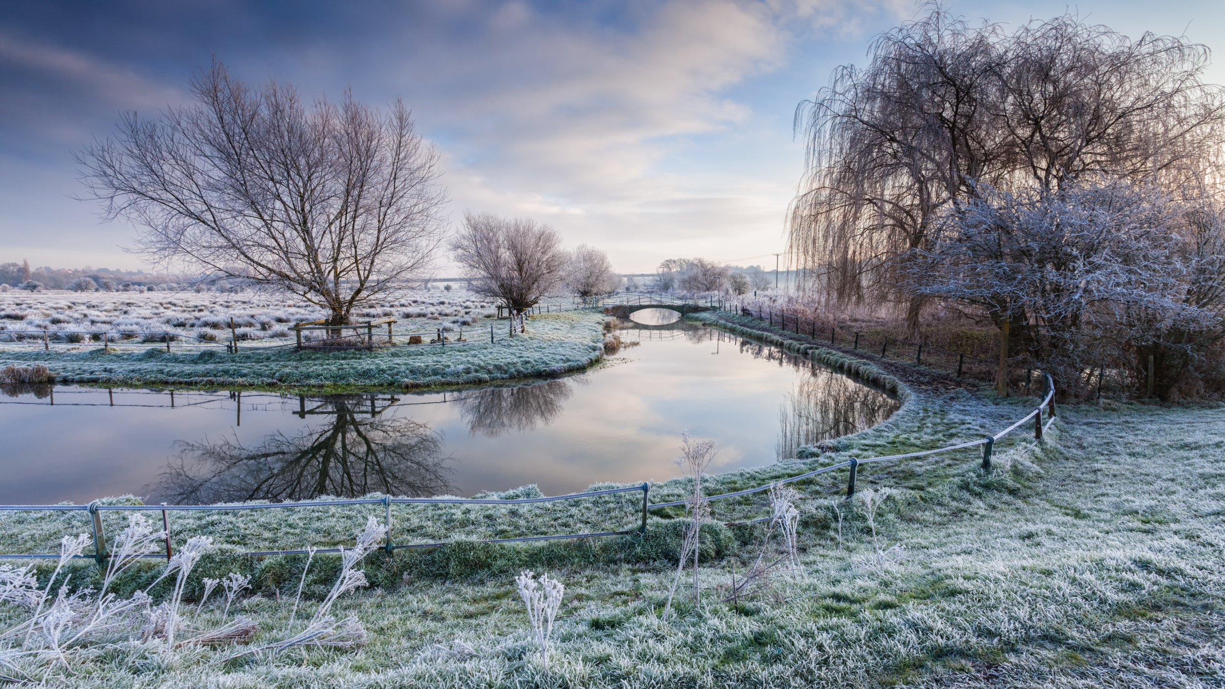 Hertford Marshes Hertford, Hertfordshire, UK. December 31,2014. Image shows a natural scene of an english river in the morning mist. The dawn sky is blue with whispy clouds, reflections of the trees can be seen in the river. Frost is scattered on the ground.