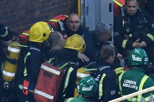 LONDON, ENGLAND - JUNE 14: A man is rescued by fire fighters after a huge fire engulfed the 24 storey residential Grenfell Tower block in Latimer Road, West London in the early hours of this morning on June 14, 2017 in London, England. The Mayor of London, Sadiq Khan, has declared the fire a major incident as more than 200 firefighters are still tackling the blaze while at least 50 people are receiving hospital treatment. (Photo by Leon Neal/Getty Images)
