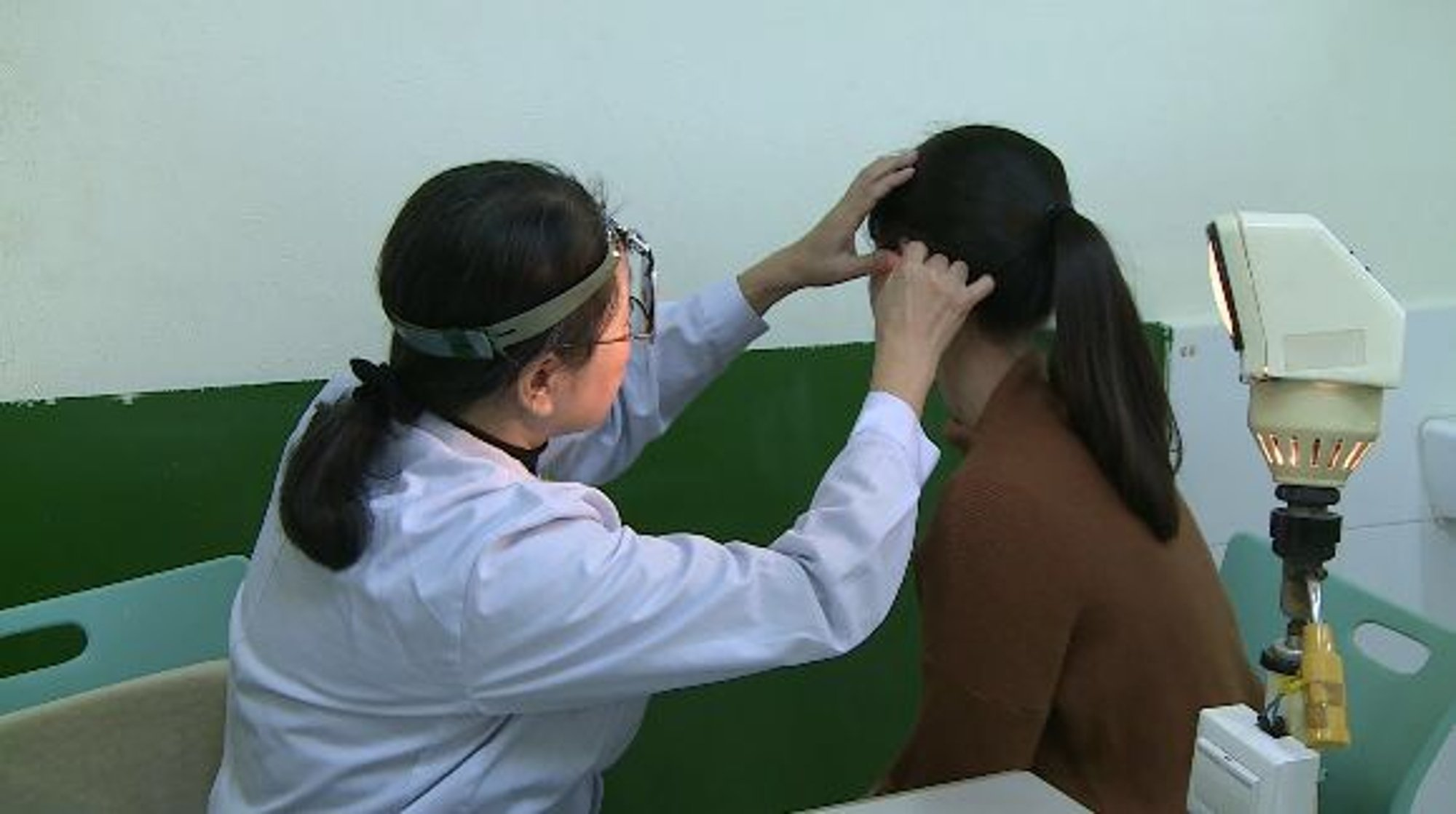 Pic shows: Doctor Lin Xiaoqing examining a female patient. CHINA: A woman admitted to hospital with apparently ???sexist??? hearing loss woke up one morning completely unable to hear the sound of men talking.