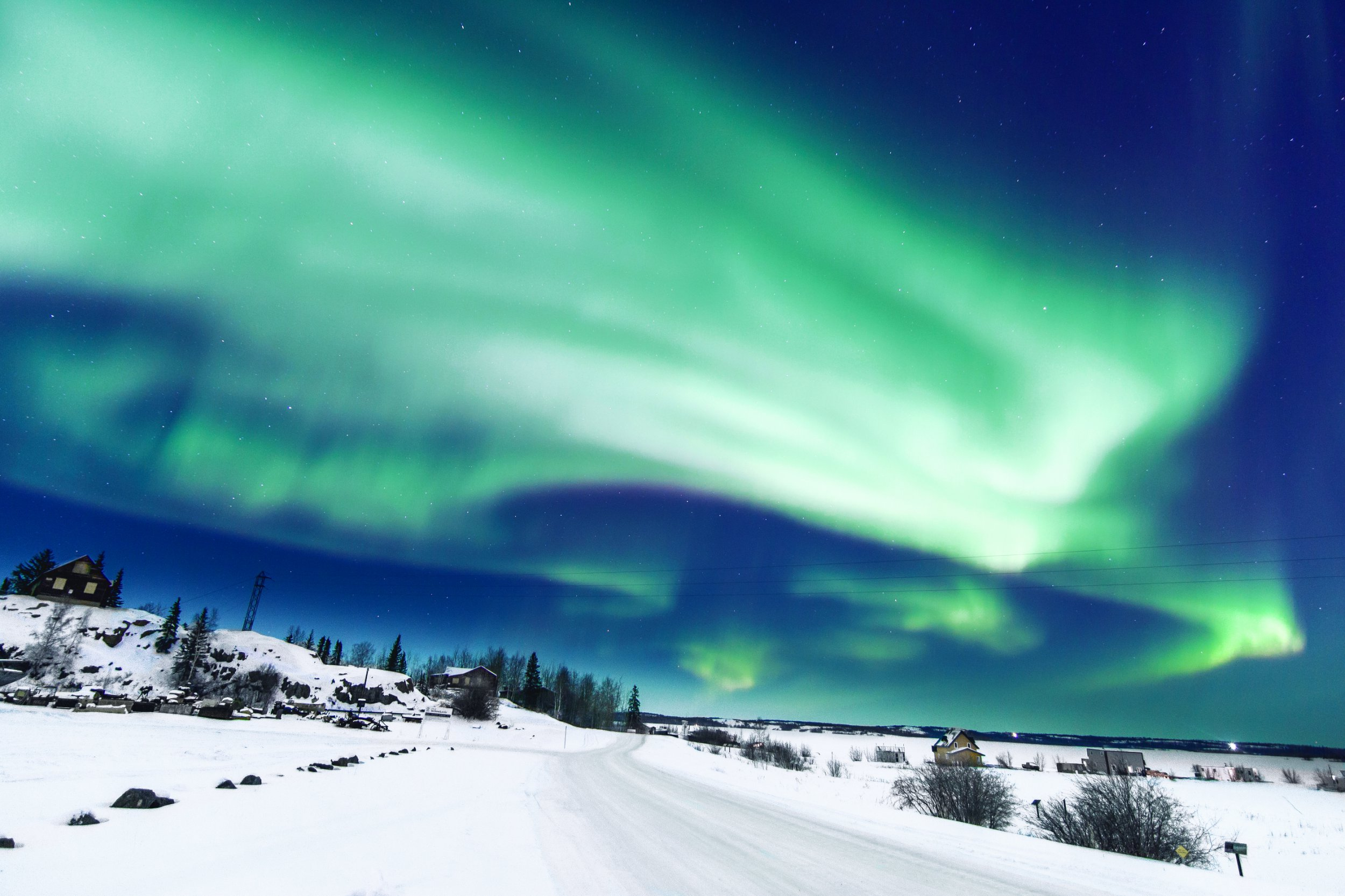 Northern Lights over a snow-covered road close to Yellowknife in the Northwest Territories in Canada.