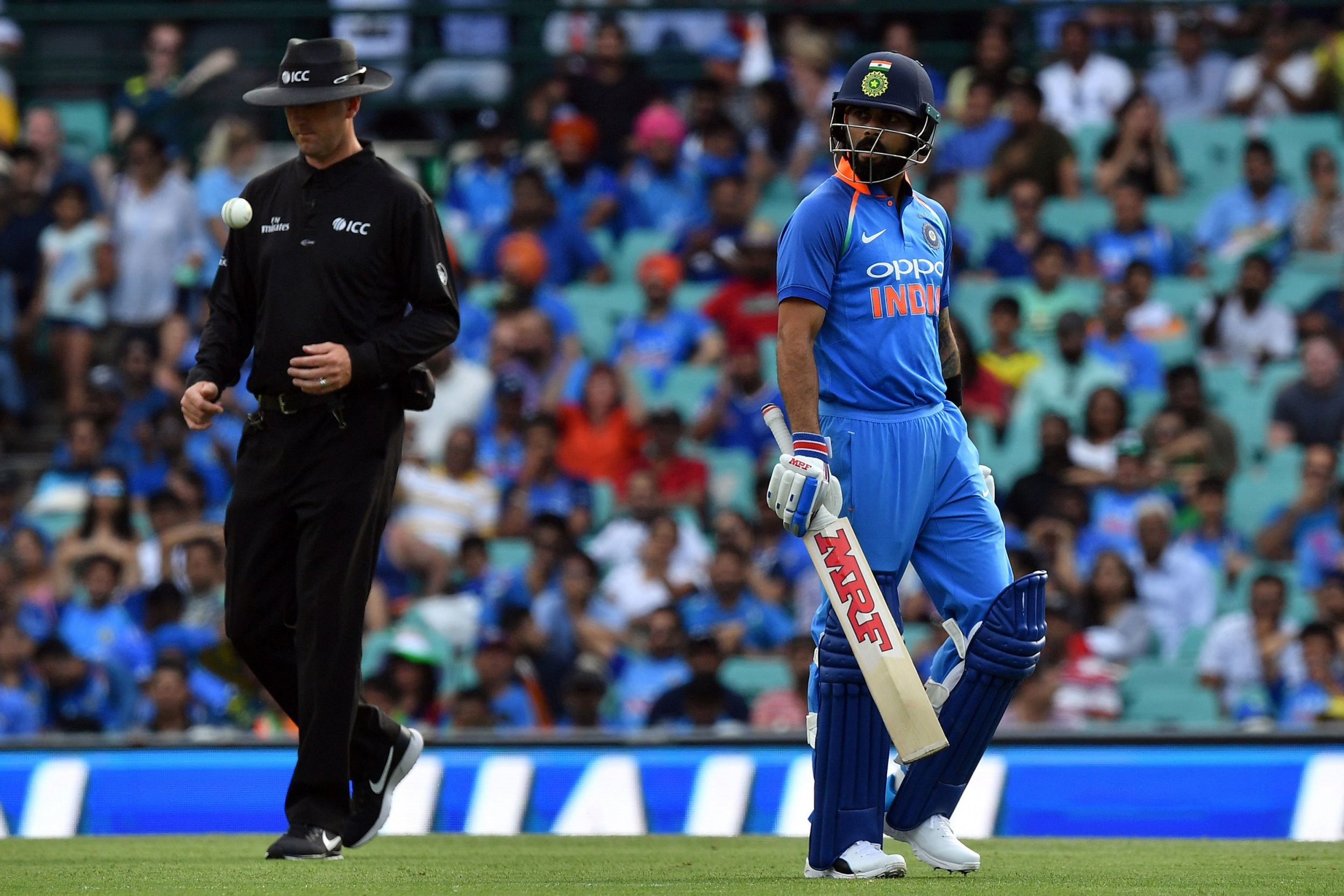 India's captain Virhat Kohli (R) walks back to the pavilion after his dismissal during the first one-day international (ODI) match between Australia and India at the Sydney Cricket Ground in Sydney on January 12, 2019. (Photo by Saeed Khan / AFP) / -- IMAGE RESTRICTED TO EDITORIAL USE - STRICTLY NO COMMERCIAL USE --SAEED KHAN/AFP/Getty Images