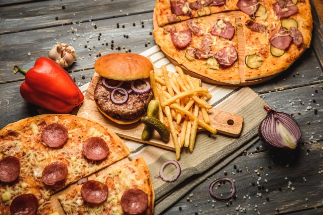 SNIFF AND SCRATCH - Just two minutes of sniffing a burger or pizza stops the cravings for junk food pizza and hamburger on wooden background with French fries red onion garlic and sweet pepper and pickles