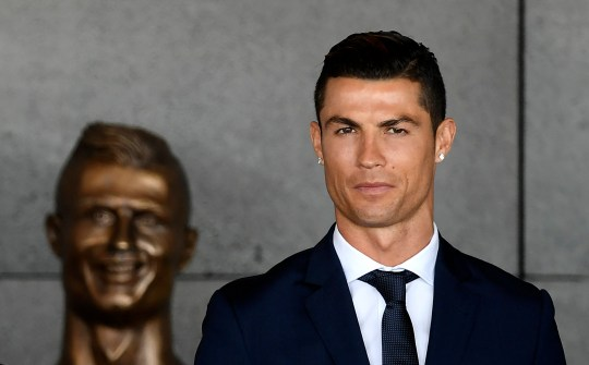 TOPSHOT - Portuguese footballer Cristiano Ronaldo stands past a bust presented during a ceremony where Madeira's airport in Funchal is to be renamed after Cristiano Ronaldo, on Madeira island, on March 29, 2017. Madeira airport, the birthplace of Portuguese footballer Cristiano Ronaldo, was renamed today in honor of the quadruple Ballon d'or and captain of the Portuguese team sacred European champion last summer. / AFP PHOTO / FRANCISCO LEONG (Photo credit should read FRANCISCO LEONG/AFP/Getty Images)