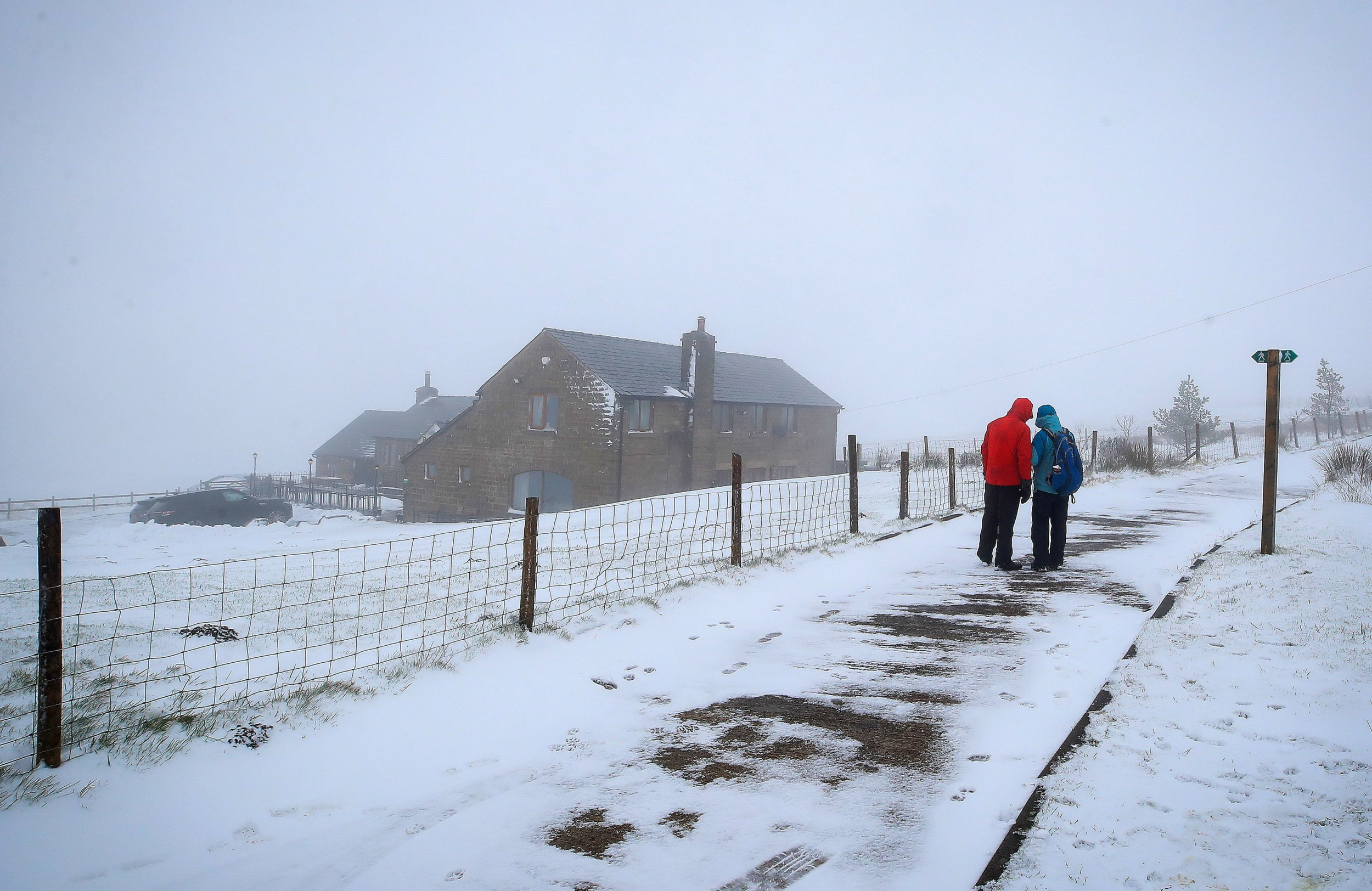 Walkers on a snow-covered path outside the Peak View tea rooms near Macclesfield, Cheshire. PRESS ASSOCIATION Photo. Picture date: Saturday January 19, 2019. The current cold spell will continue over the weekend, with largely grey, gloomy conditions and patches of rain and sleet in southern areas on Saturday, according to the Met Office. See PA story WEATHER Cold. Photo credit should read: Peter Byrne/PA Wire