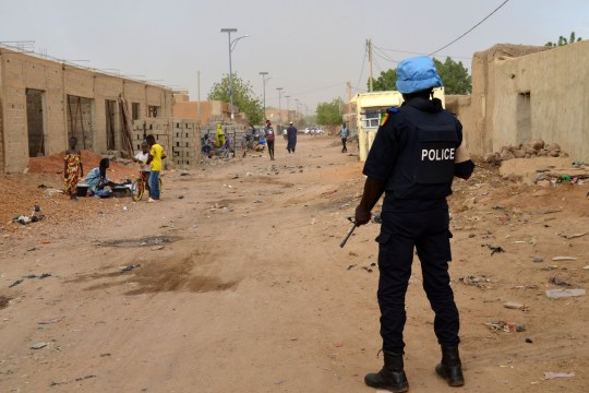 TOPSHOT - A UN soldier with the Senegalese contingent of the United Nations Multidimensional Integrated Stabilisation Mission (MINUSMA)in Mali patrols the streets of Gao on July 23, 2018. (Photo by Souleymane Ag Anara / AFP) (Photo credit should read SOULEYMANE AG ANARA/AFP/Getty Images)