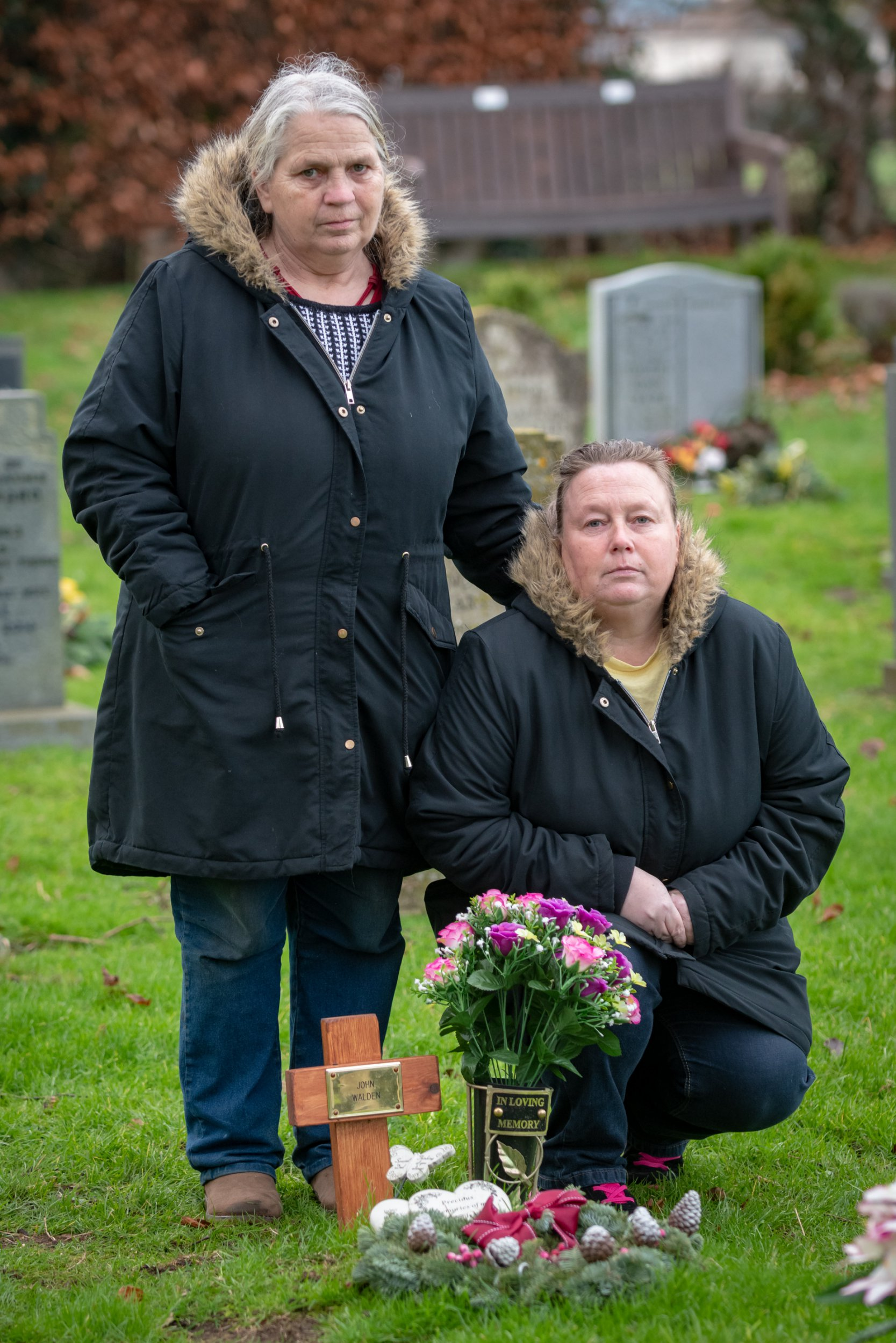 """(L-R) Pauline Walden, 64, with her daughter Caroline Walden,45, by the grave of Pauline???s husband John Walden at St Mary???s Church Syderstone Norfolk. See SWNS story SWSYgrave..A grieving family has been told they can't put the words 'dad' or 'grandad' on their loves ones grave -- because it's against church policy.A grieving daughter claims that a suggestion by a local reverend to use """"father"""" and """"grandfather"""" on their grave is an insult to their family.Caroline Walden, whose dad's passed away in January aged 65 from COPD want the headstone to read """"loving husband, dad, and grandad"""" at his burial site at St Mary's Church in Syderstone, Norfolk.However, the family claim that the rector rejected their request because of """"policy"""" and said that they should call themselves """"grandfather"""" and """"father"""" instead because of local church policy."""
