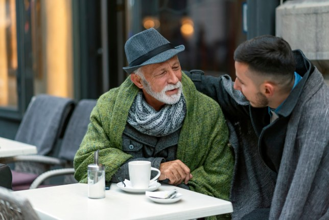 Photo Of Positive Aged Man And His Grandson Resting In The Cafe During Winter Day. Joyful Delighted Man And His Grandfather Resting In The Cafe.