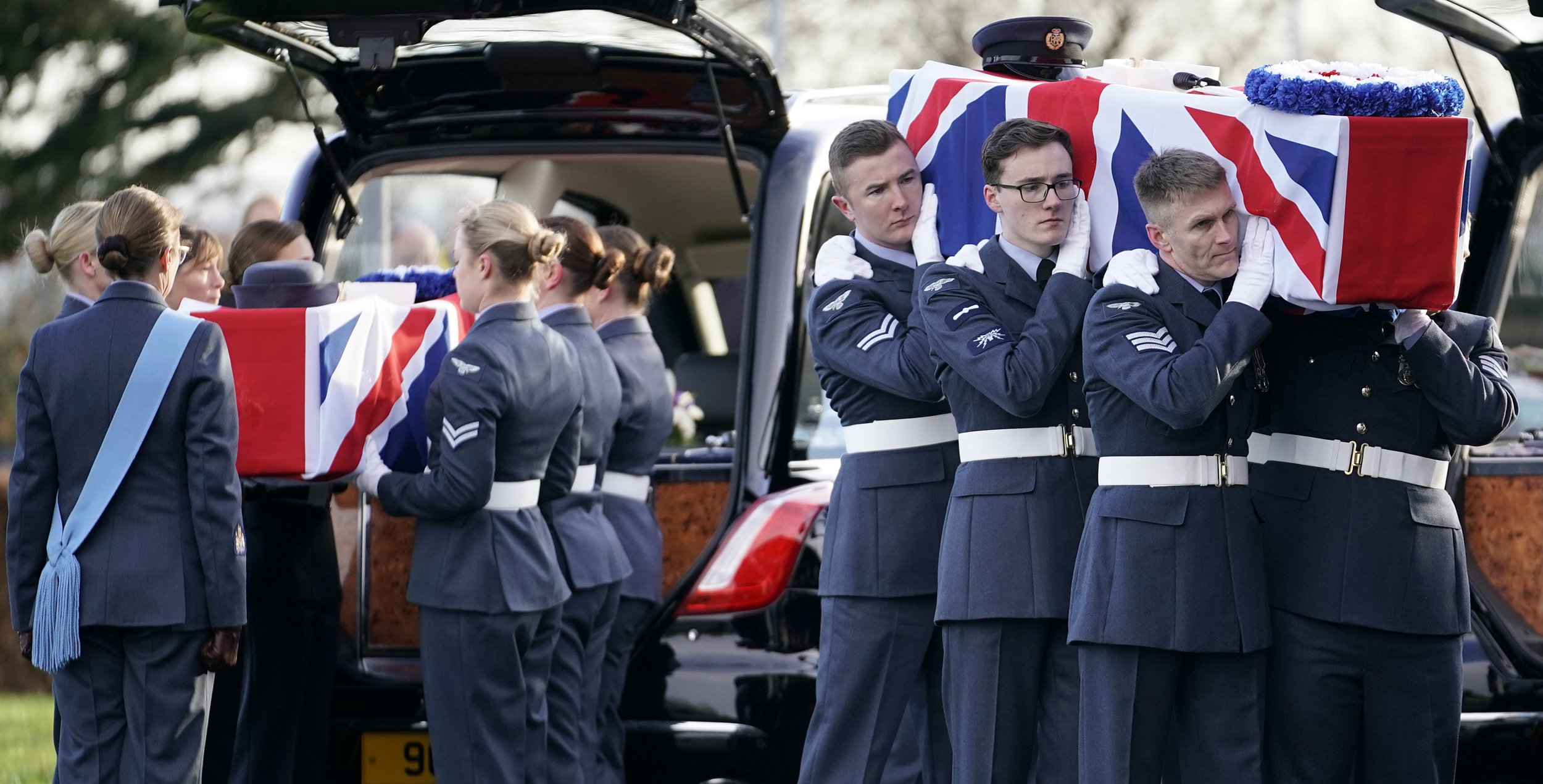 TELFORD, ENGLAND - JANUARY 22: Royal Air Force pall bearers from RAF Cosford carry the coffin of World War II veterans Victor Barnett (R) and his wife Edna during their funeral service at Telford Crematorium on January 22, 2019 in Telford, England. Victor Barnett, aged 101, was a Dambusters engineer and his wife Edna, 91, a member of the Womens Auxiliary Air Force and worked in air traffic control during World War II. The couple from Telford, Shropshire died within days of each other and had no surviving relatives to come to their funeral. A 'call to arms' by airmen at RAF Cosford saw hundreds of people arrive to pay their respects to the couple. (Photo by Christopher Furlong/Getty Images)