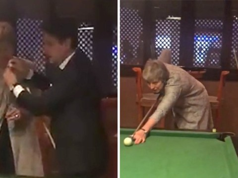 Theresa May attempts to play pool during downtime at EU summit