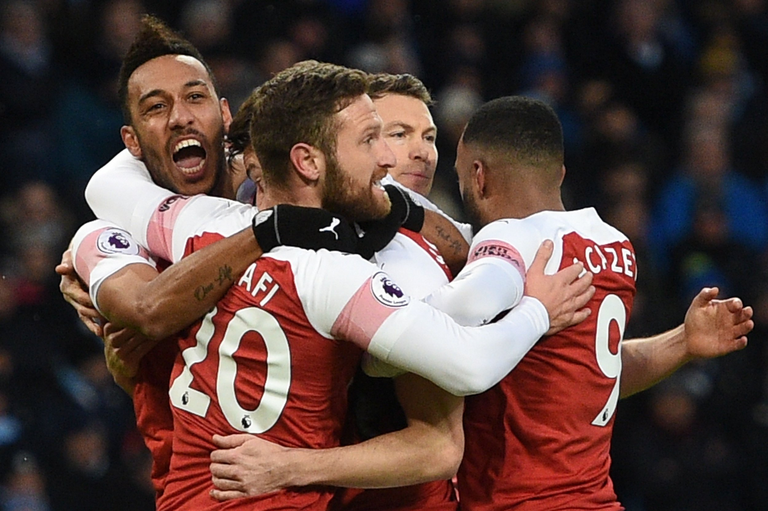 Arsenal's French defender Laurent Koscielny (C) celebrates with teammates after scoring their first goal during the English Premier League football match between Manchester City and Arsenal at the Etihad Stadium in Manchester, north west England, on February 3, 2019. (Photo by Oli SCARFF / AFP) / RESTRICTED TO EDITORIAL USE. No use with unauthorized audio, video, data, fixture lists, club/league logos or 'live' services. Online in-match use limited to 120 images. An additional 40 images may be used in extra time. No video emulation. Social media in-match use limited to 120 images. An additional 40 images may be used in extra time. No use in betting publications, games or single club/league/player publications. / OLI SCARFF/AFP/Getty Images
