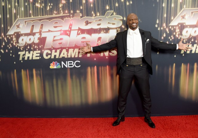 terry crews in front of the america's got talent the champions logo