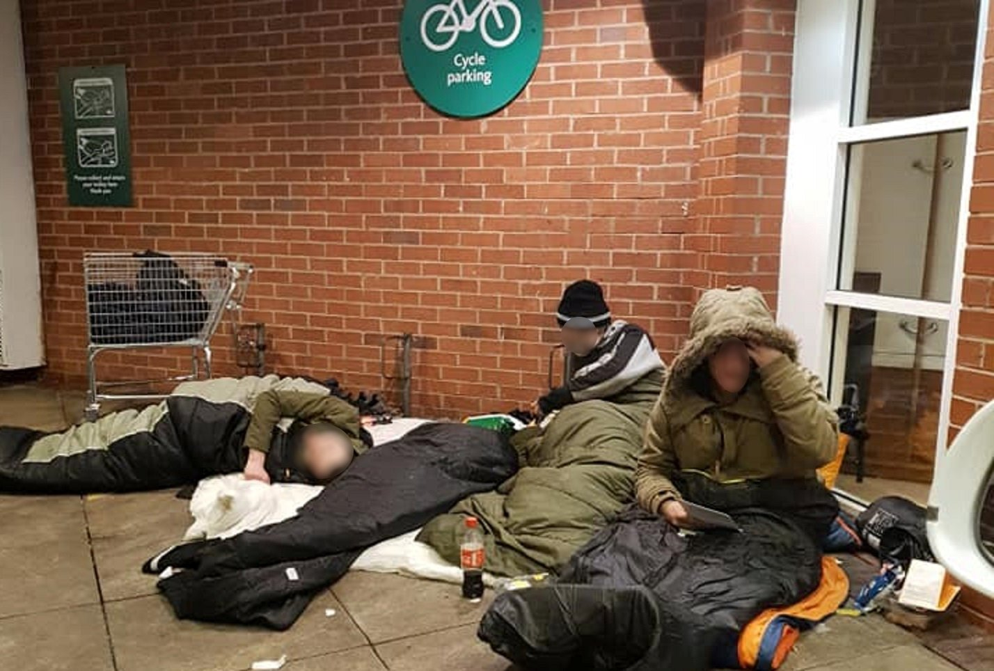 Homeless people outside Morrisons in Blackburn. See SWNS story SWLEhomeless; Managers at a Morrisons store in Blackburn, Lancs., and a Sainsbury's in Halifax, West Yorks., have both confessed to claims staff had been disposing of tents and property outside their stores. Uniformed staff were spotted loading items into a trolley from inside a ventilation unit where rough sleepers are known to store their belongings throughout the day.