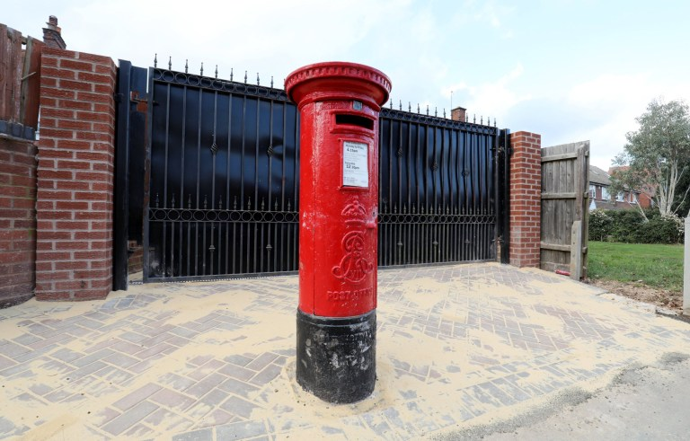 A home owner is at the centre of a first class row - after building work left a vintage postbox stuck in the MIDDLE of his driveway. See SWNS story SWMDmailbox. The un-named resident spent thousands of pounds widening the driveway to his home and having a set of gates installed next to an old, red pillar post box. But the work has made the distinctive 100-year-old postbox stick out like a sore thumb and attracted criticism from local residents. The red pillar has been sited on a newly-laid block paving at the corner of Oxford Road and School Road, Moseley, Birmingham. Local councillors have received complaints about the work and are investigating whether it meets planning regulations. The homeowner, who has declined to be named, has applied to Royal Mail to get the postbox relocated.