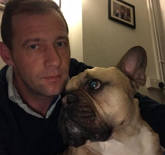 """BNPS.co.uk (01202 558833) Pic: GaryWells/BNPS Bulldog Gus with owner Gary Wells. A dog owner got a surprise when his """"dopey"""" pet dug up a Second World War shell on the beach. Gary Wells, 37, said his French bulldog Gus is never normally interested in picking up sticks, chasing balls or digging holes so he was surprised when the four-year-old pup started digging in the sand at Studland beach, Dorset. The protective pooch then tried to keep his owner away from the metal object he had found, pushing his body against him and preventing him from getting to the hole. Eventually Mr Wells, a care manager from Langton Matravers, was able to get a look at the ordnance and immediately called the emergency services."""