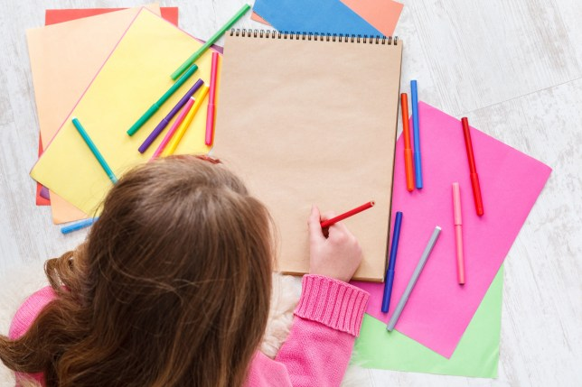 Writing letter to santa. Beautiful girl makes wish list of presents for christmas. Drawing picture. Prepare for winter holidays, top view of child on floor