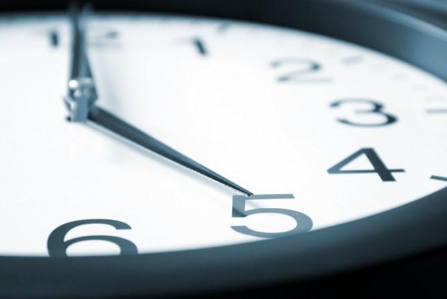 A macro shot of a clock striking five.