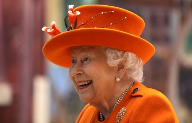 The Queen smiling and wearing an orange hat and jacket in London