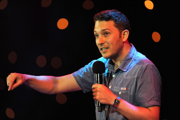 Jon Richardson holding a microphone on stage at The Mencap Big Comedy Special
