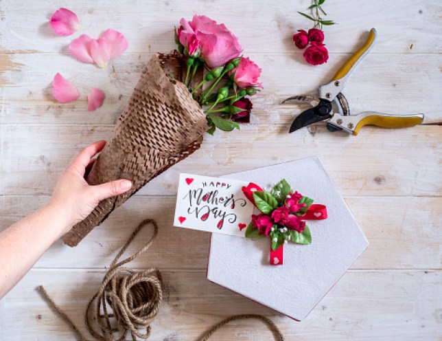 Hand laying on the table bunch of roses and box with a gift for mother's day