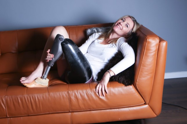 Rebecca Legon, a 38-year-old amputee, poses on a sofa
