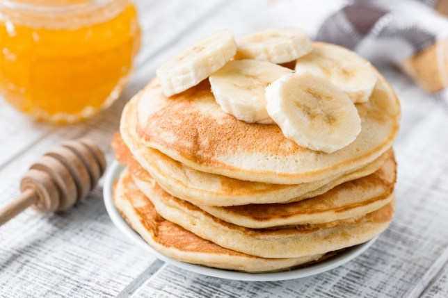 A stack of pancakes with banana and honey