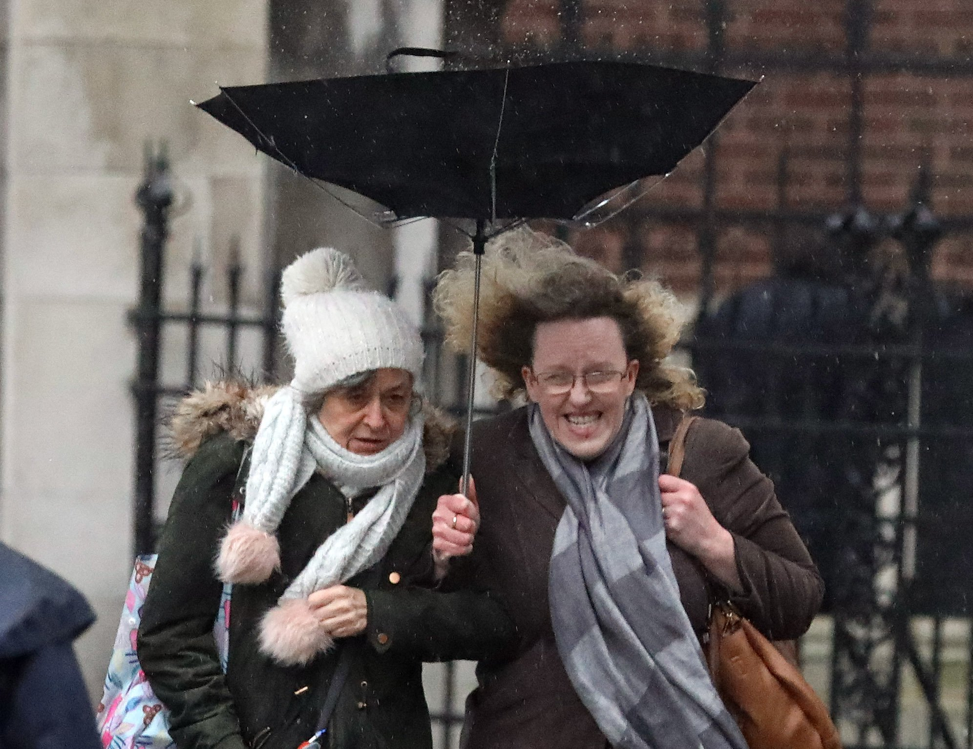 two women use a broken umbrella in a storm