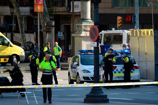 """TOPSHOT - Medical staff members and policemen stand in a cordoned off area after a van ploughed into the crowd, injuring several persons on the Rambla in Barcelona on August 17, 2017. - Police in Barcelona said they were dealing with a """"terrorist attack"""" after a vehicle ploughed into a crowd of pedestrians on the city's famous Las Ramblas boulevard on August 17, 2017. Police were clearing the area after the incident, which has left a number of people injured. (Photo by Josep LAGO / AFP) (Photo credit should read JOSEP LAGO/AFP/Getty Images)"""