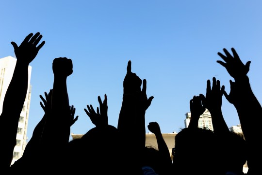 community initiative or concert concept, hands of group of people in the sky, silhouette