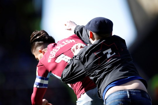 """A fan invades the pitch and attacks Aston Villa's Jack Grealish during the match Soccer Football - Championship - Birmingham City v Aston Villa - St Andrew's, Birmingham, Britain - March 10, 2019 Action Images/Carl Recine EDITORIAL USE ONLY. No use with unauthorized audio, video, data, fixture lists, club/league logos or """"live"""" services. Online in-match use limited to 75 images, no video emulation. No use in betting, games or single club/league/player publications. Please contact your account representative for further details."""