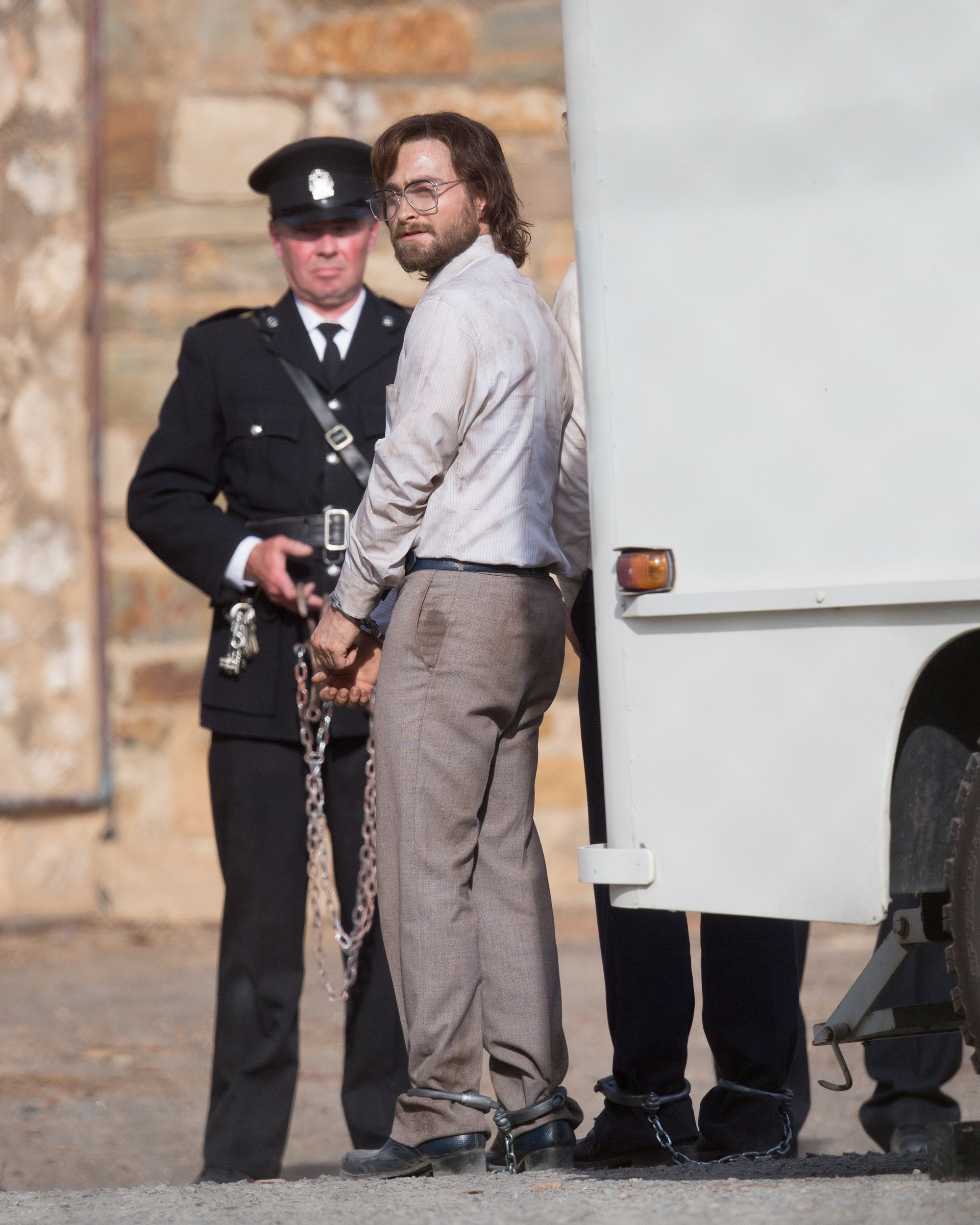 """EXCLUSIVE: Daniel Radcliffe was looking worse for wear as he got into character for filming of """"Escape from Pretoria"""" in Adelaide. Daniel was looking scruffy as he wore a very dirty business shirt tucked into his pants with a tie and grey pants with a pair of eye glasses. His co-star had a bloodied face. The filming took place at the old Adelaide Gaol which has been transformed into Pretoria prison for filming. Daniel and his co-star in the scene were shackled as they exited a white van and were met by many officers. Daniel's character had his legs shackled as well as his hands in parts of the scene. It's a far different look from the boy who was once Harry Potter. Filming will continue over the next few weeks in Adelaide. 11 Mar 2019 Pictured: Daniel Radcliffe. Photo credit: MEGA TheMegaAgency.com +1 888 505 6342 (Mega Agency TagID: MEGA378145_001.jpg) [Photo via Mega Agency]"""
