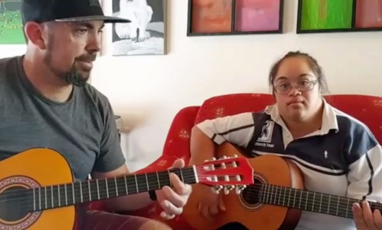 PIC FROM ROB MULLEN / CATERS - (Pictured: Rob Mullen and his pupil, Robyn) - This selfless musician has become an internet sensation having performed a number of hit singles with people with learning difficulties such as Downs syndrome. Rob Mullens unique style of teaching has seen him produce covers of Robbie Williams, One Republic, Snow Patrol, and Jason Mraz - all thanks to the help of some willing volunteers. Through his work, Rob, 41, from Hamilton, New Zealand, has helped those who had never even considered a musical future to sing, play instruments and even rap. One of his star pupils, Alex Johnsen, 27, even went viral with the teacher, after the pair produced a cover of Snow Patrols Chasing Cars that was seen around the world. - SEE CATERS COPY