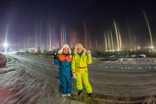 *MANDATORY BYLINE* PIC FROM Valentin Zhiganov / Caters News - (PICTURED: Two women pose with the vertical auroras, also known as light pillars, and normal auroras, near the city of Apatity in Russia. PIC TAKEN ON 02/02/19)- Two girls were captured admiring a stunning vertical aurora phenomenon while soaking in a hot tub.Valentin Zhiganov, 44, shot the incredible pictures of the rare optical illusion near his home city of Apatity in Murmansk Oblast, Russia in temperatures of minus 30 degree Celsius. His images show the aurora also known as light pillars mixing with the lights of the city while the local power plant looms in the background.SEE CATERS COPY