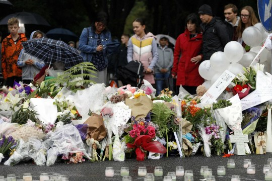 People gather in front of floral tributes at a makeshift memorial for victims of the March 15 mosque attacks, in Christchurch on March 17, 2019. - The death toll from horrifying shootings at two mosques in New Zealand rose to 50, police said March 17, as Christchurch residents flocked to memorial sites and churches across the city to lay flowers and mourn the victims. (Photo by Tessa BURROWS / AFP)TESSA BURROWS/AFP/Getty Images