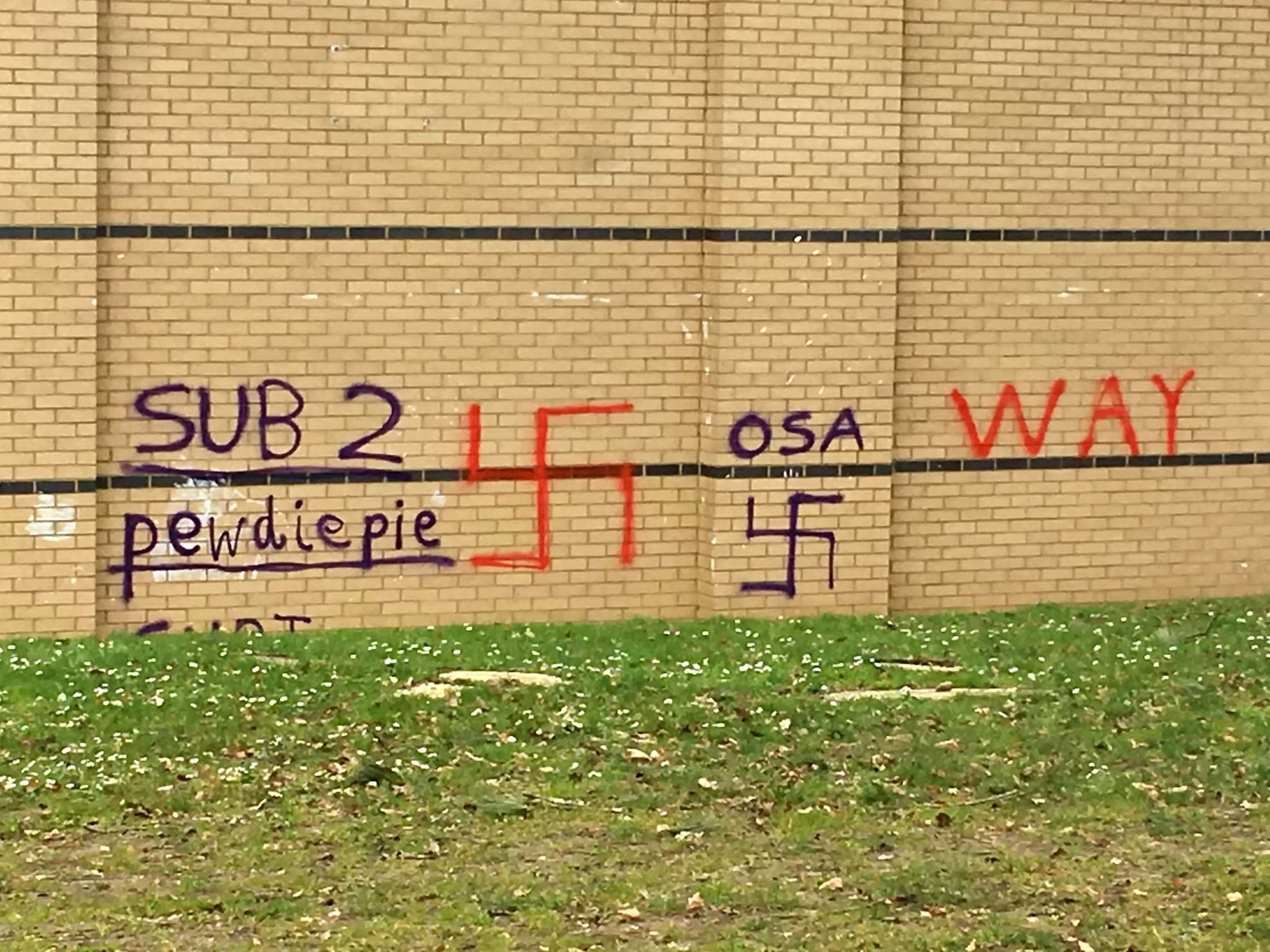 Vandals have scrawled Nazi swastikas and a shocking reference to the horrific New Zealand shooting massacre on the side of a school in Oxford. See SWNS story SWBRnazi; SWASTIKAS have been scrawled across a school wall in Oxford. The Nazi graffiti was spotted daubed on a back wall of Cheney School in Headington today. It sits alongside further offensive wording including obscenities and a nod to Swedish YouTuber 'PewDiePie' - a reference reportedly made during the New Zealand shootings on Friday. It is believed a gunman involved in the attack on a mosque in Christchurch, New Zealand, in which 49 people were killed, urged people to subscribe to 'PewDiePie' before opening fire.